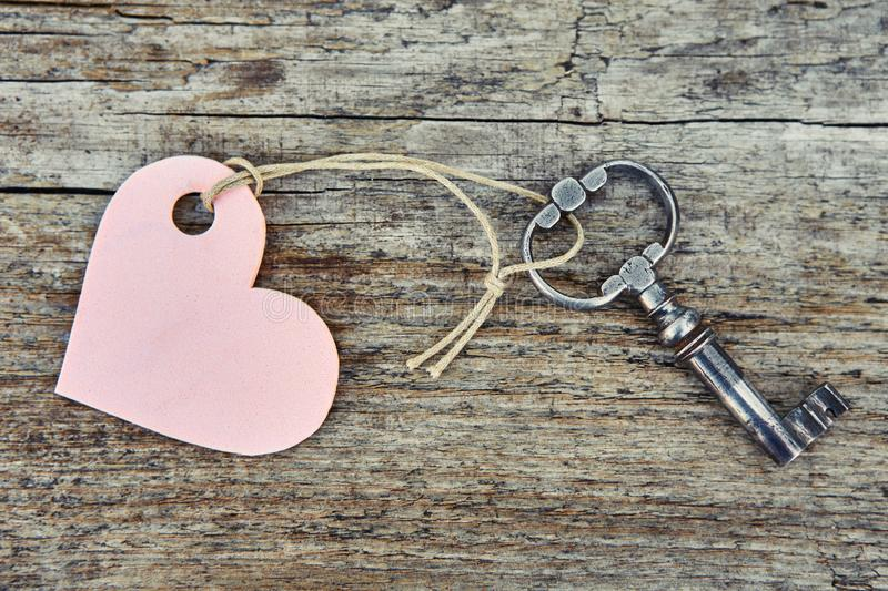 An antique handmade key with a heart-shaped label keychain lies on a wooden Board.  stock images
