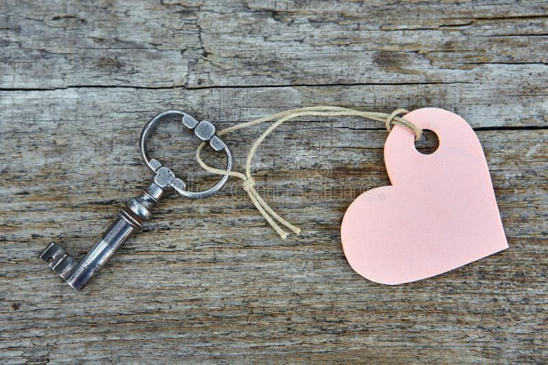 An antique handmade key with a heart-shaped label keychain lies on a wooden Board.  stock image