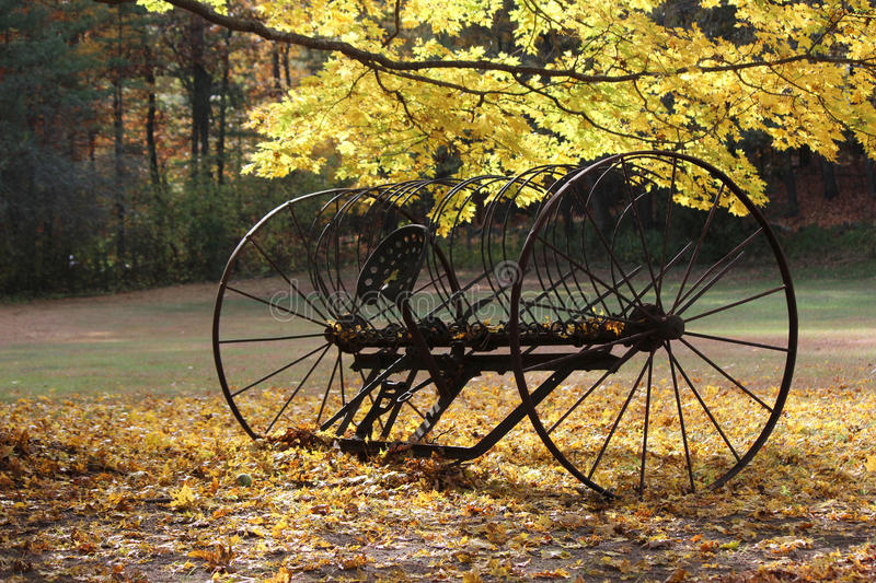 Antique Hay Rake in Fall. A rusty old antique hay rake in a yard in New England in Fall stock photos
