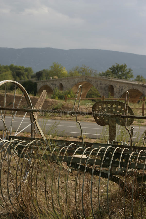 Antique Haymaker by a bridge in the Luberon France. Tractor seat and old bridge with Luberon hills behind stock photos
