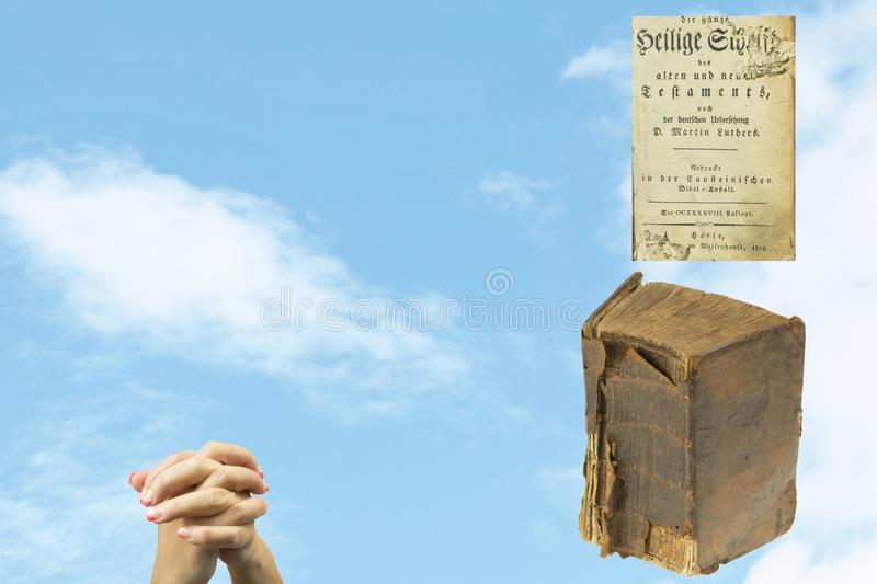 Antique Holy bible and praying hands of a woman over blurred sky stock image