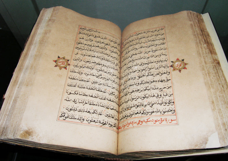 Antique holy book of Islam. A beautiful old antique holy book of the Islam religion, opened and showing at close up the beauty of the arabic calligraphy script royalty free stock photo