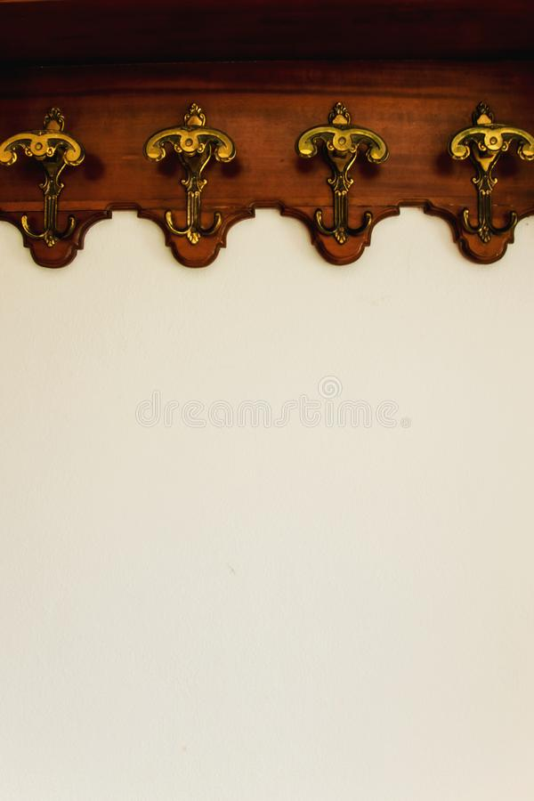 Antique hooks on the white wall. Space for text stock images