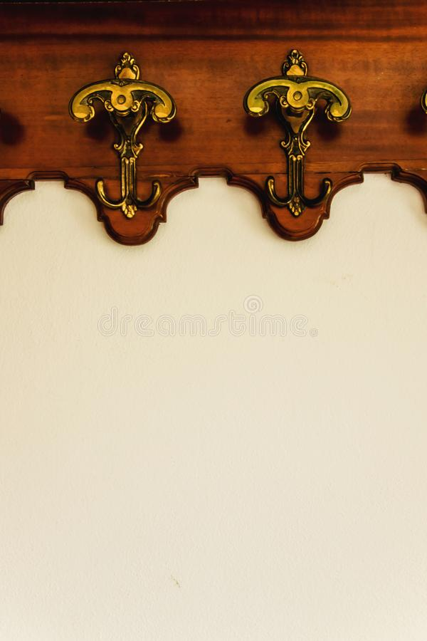 Antique hooks on the white wall. Space for text stock photo