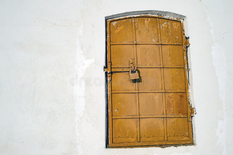 Antique iron-bound window with a latch. Background. Antique iron-bound window with a latch. The concept of the template is hidden or falsified secrets of history stock photography