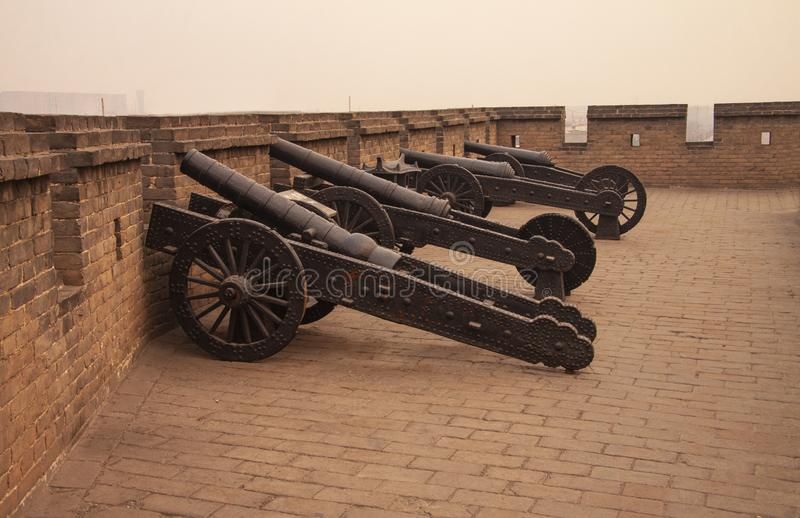 Antique iron cannons at the last remaining intact Ming Dynasty city wall in China the Chinese city Pingyao, Shanxi Province. Old c. Hinese military facilities stock photography