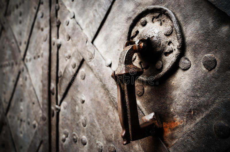 Antique iron castle door. Antique iron knocker on a medieval castle door stock photography