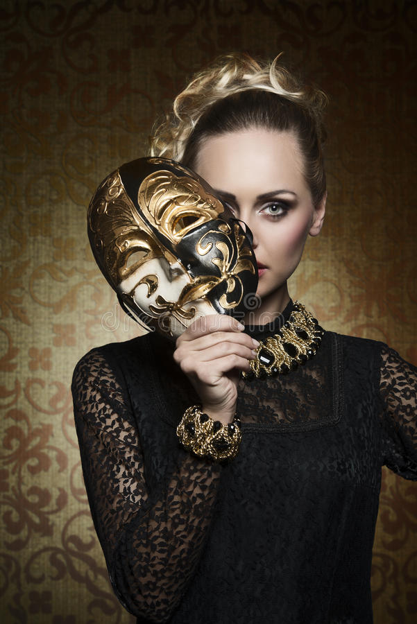Antique lady with gothic mask. Cute blonde female with antique lady style covering her face with precious mask and looking in camera. Wearing gothic lace dress stock images
