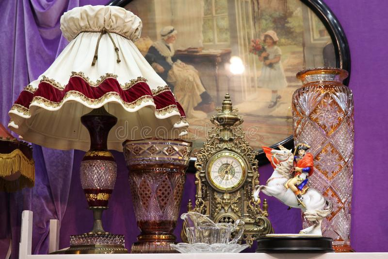 Antique lamp with lampshade, clock and large glass vases stock image