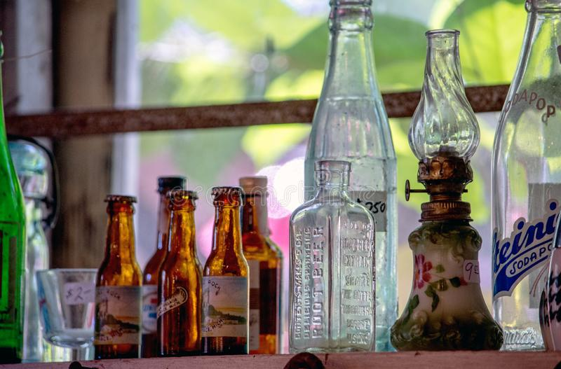 Antique lamps and bottles in a window stock photography