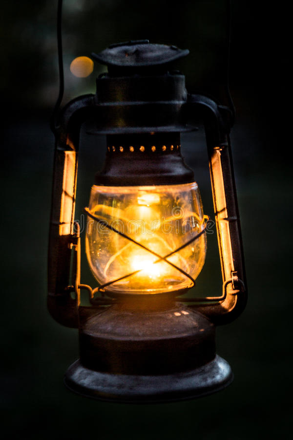 Antique Lantern. An antique lantern glows against a dark background, with orange glow royalty free stock image
