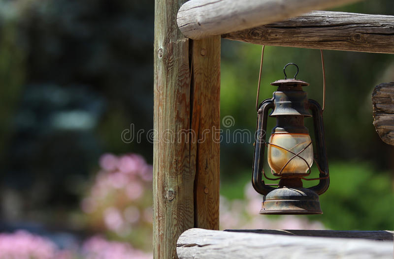 An antique lantern. An antique lantern hung from a lodge pole fence witha blurred background of beautiful bokeh royalty free stock photos