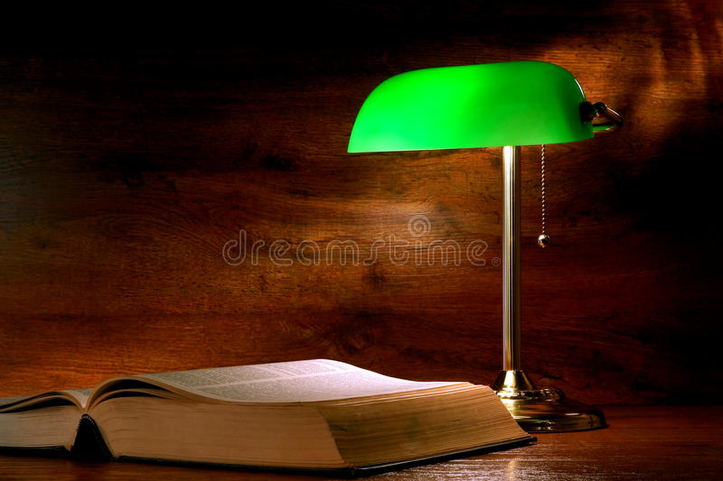 Antique Library Study Book and Old Banker Lamp. Big antique library study book under the soft light glow of a traditional old style banker lamp with green glass stock photos