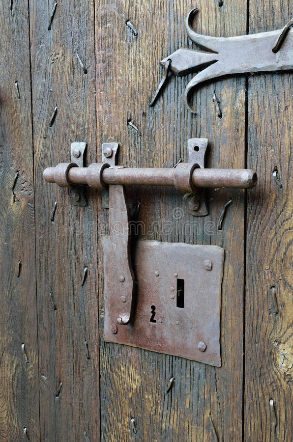 Antique lock with a hasp on the timber entrance. The old-style big metal lock with a latch on the wooden surface of the ancient batten door stock image
