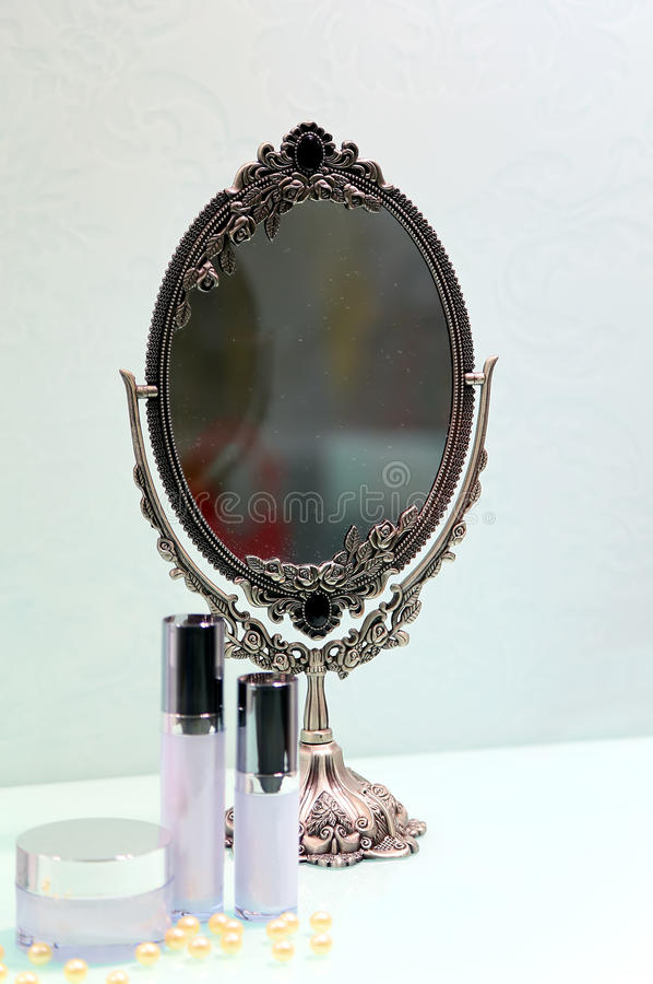 Antique make up mirror. With blurred make up accessories royalty free stock photography