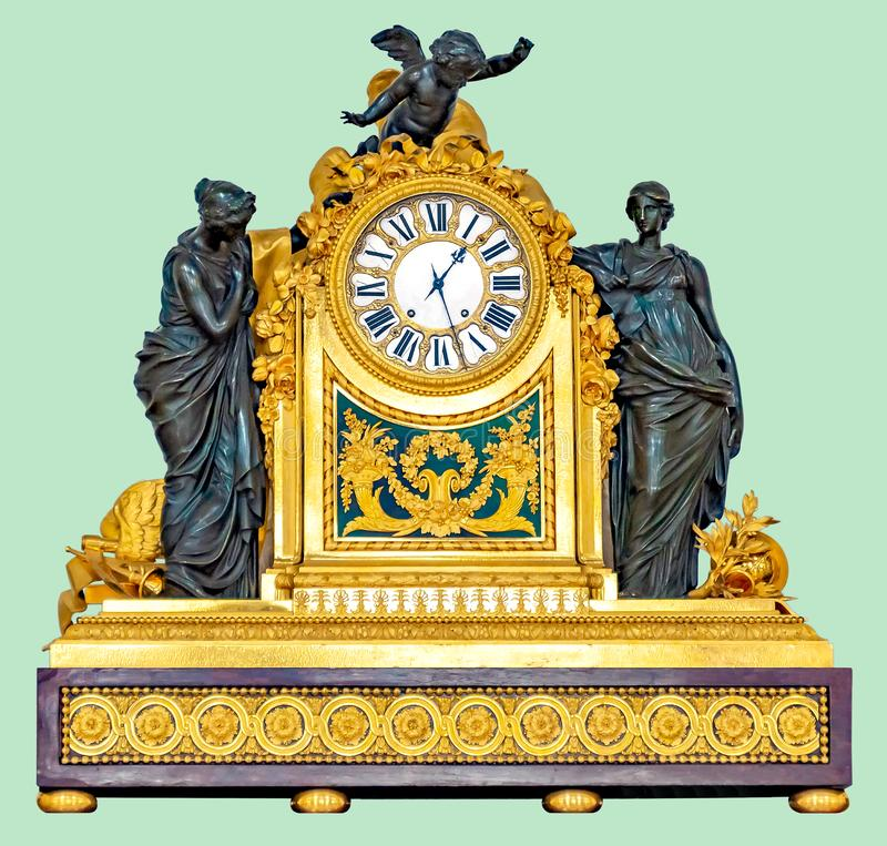 ANTIQUE MANTEL CLOCK WITH BRONZE STATUETTES. Antique golden mantel clock with cupid and ladies statuettes, on isolated green background with clipping path stock photography