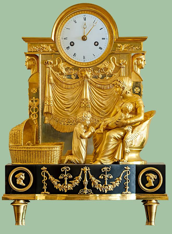 ANTIQUE MANTEL CLOCK WITH GOLDEN STATUETTES. Of a woman and children on isolated green background with clipping path stock images