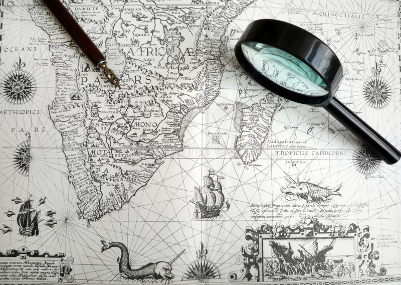 Antique Africa map and manuscript pen. A photograph of an old ancient African continental map taken with an antique calligraphic writing pen and magnifying glass royalty free stock photography