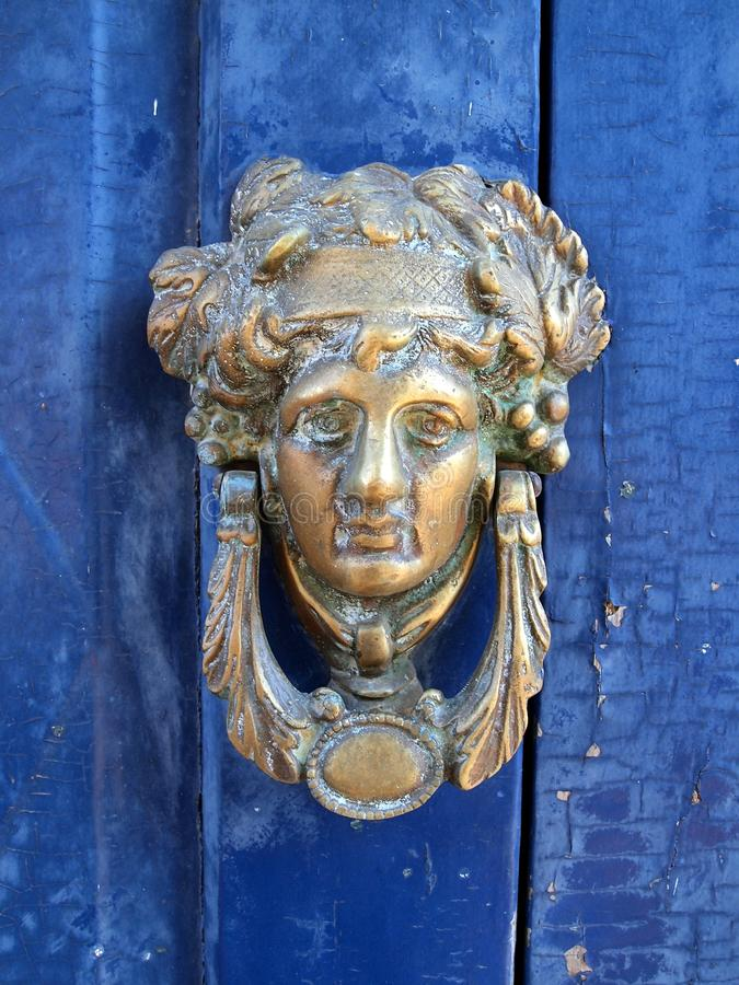 Antique Metal Door Knocker, In The Shape Of a Womans Head, Galaxidi, Greece. Antique metal door knocker, in the shape of a womans head, on a blue painted wooden royalty free stock photography