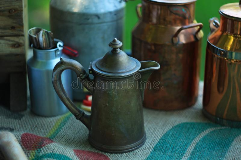 Antique metal jugs and aluminum and copper milk cans on linen tablecloth. royalty free stock photo