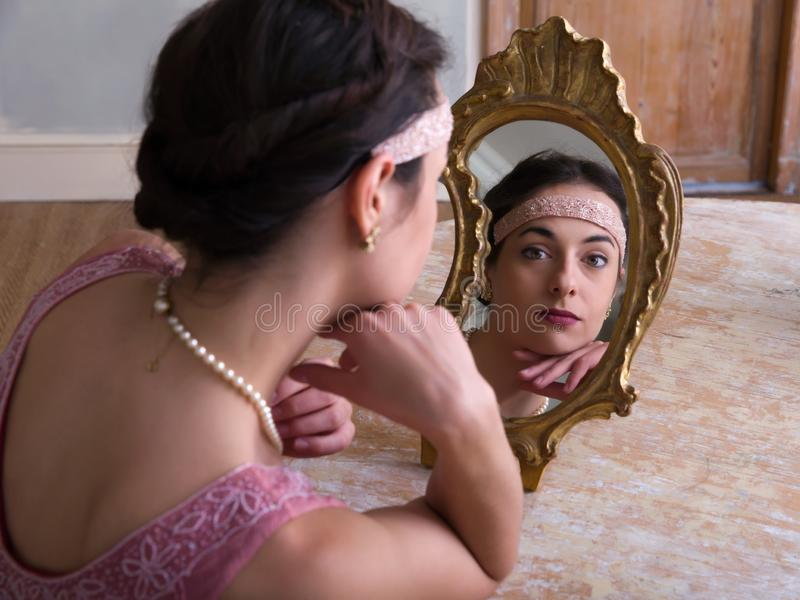 Antique mirror and classy lady. Sensual young woman in 1920s flapper dress and headband looking in an antique mirror royalty free stock images