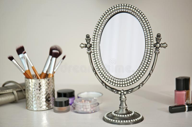 Antique mirror and cosmetics. On table royalty free stock photo