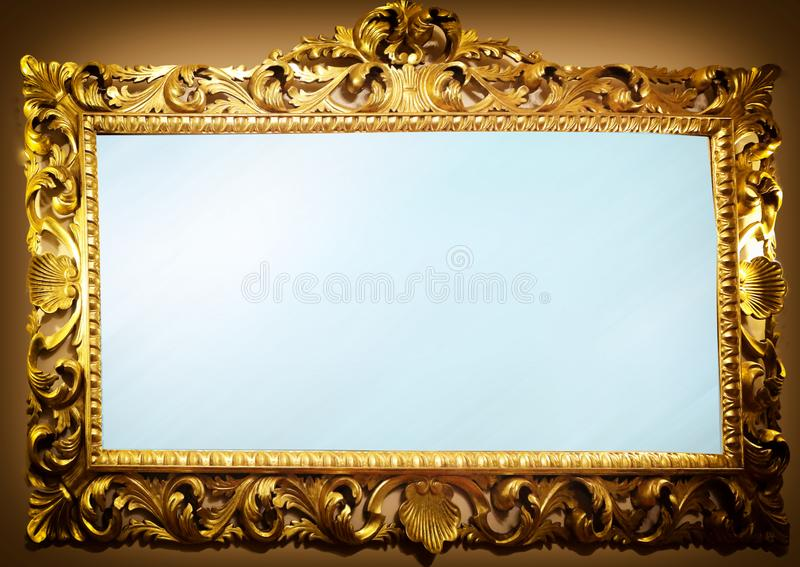 Antique mirror with frame. Antique mirror with golden wooden carved frame royalty free stock image