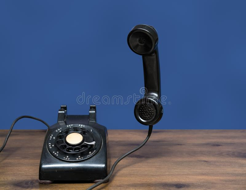 Antique old rotary dial telephone on wooden desk stock image