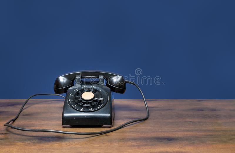 Antique old rotary dial telephone on wooden desk royalty free stock photos