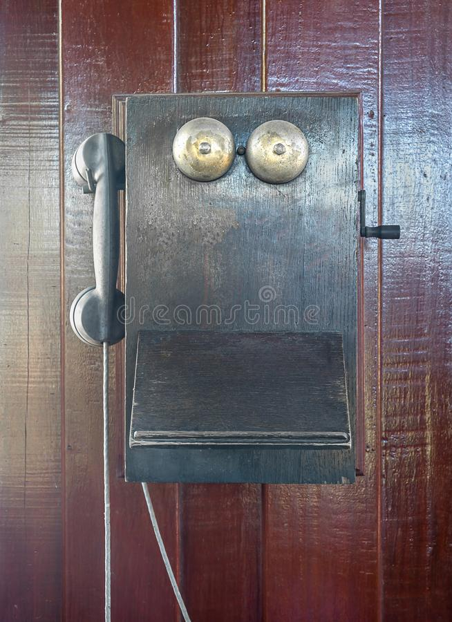 Antique old telephone hang on wooden wall royalty free stock photography