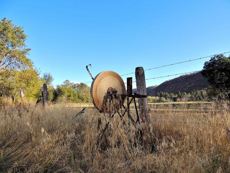 Antique peddle powered tool sharpener sitting in the weeds royalty free stock photos