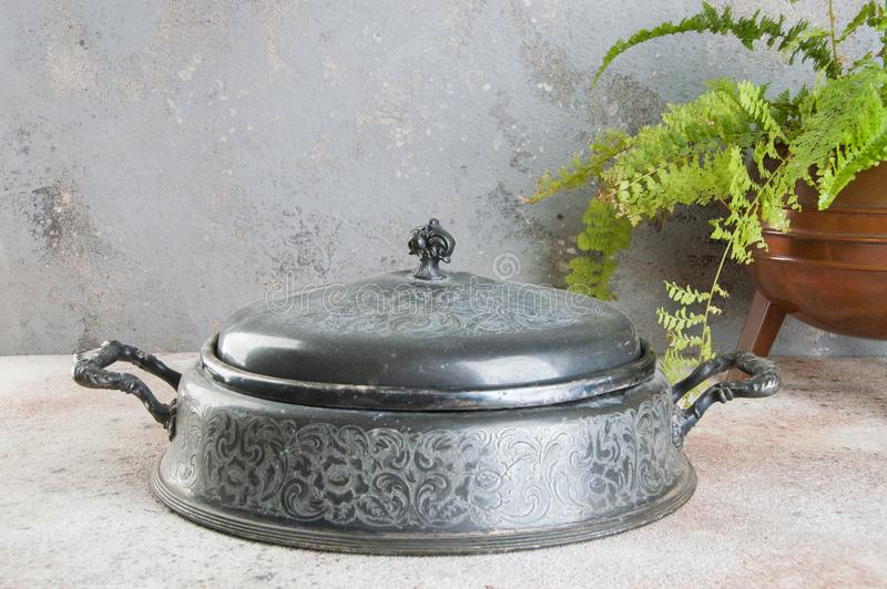 Antique pewter chafing dish holder. Candle warming stand for chafing dish, buffet table dish warmer, food photography props on a concrete background. Copy space royalty free stock image