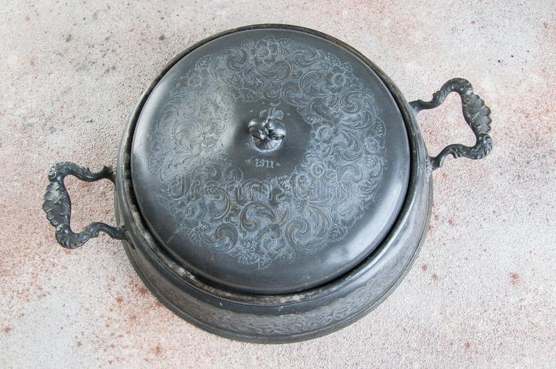 Antique pewter chafing dish holder. Candle warming stand for chafing dish, buffet table dish warmer, food photography props on a concrete background. Copy space stock photo