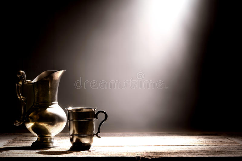 Antique Pewter Pitcher and Old Silver Drinking Cup stock images