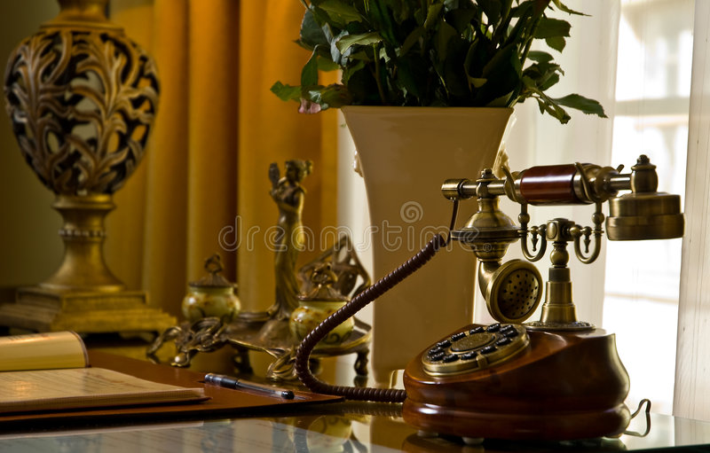 Antique phone on a desk. An antique phone on a desk in an office royalty free stock images