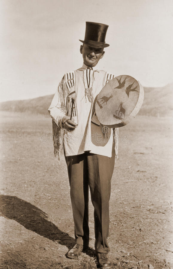 Antique photograph of a man in top hat. Original antique photograph of a man wearing a silk top hat and Indian jacket, holding an Indian drum. Taken circa 1930 stock images