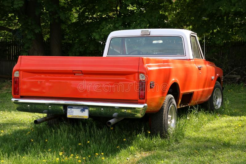 The antique pick-up truck is orange. The antique pick up truck is parked near the green trees in the high grass royalty free stock photos