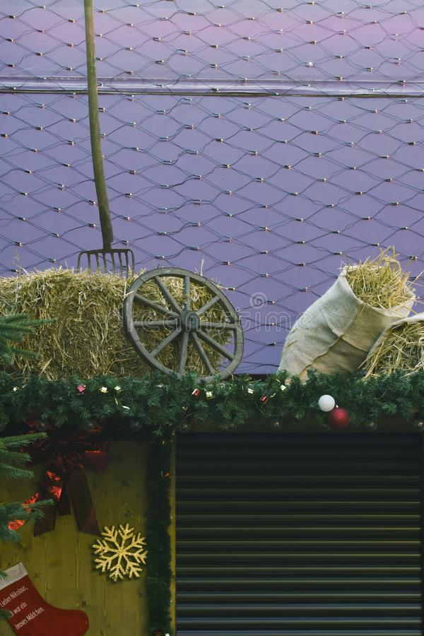 Antique pitchfork and wooden wheel hub on a hay stack. Decoration on a german christmas market royalty free stock photos