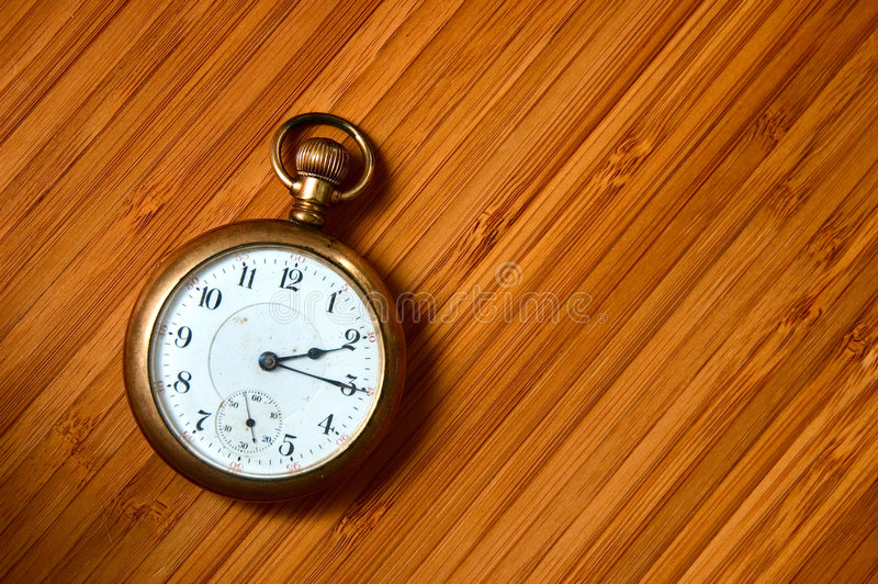 Antique pocket watch. Closeup on very old pocket watch on wooden surface royalty free stock photography