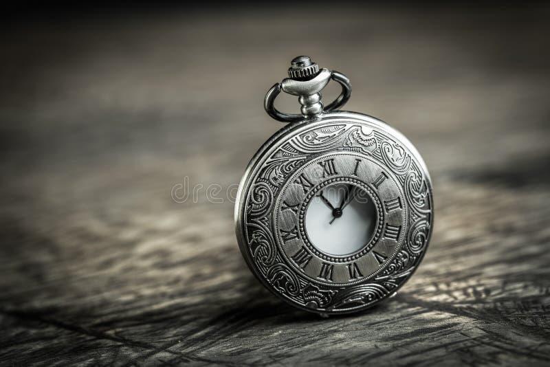 Antique pocket watch. Vintage Antique pocket watch on grunge wooden background stock images
