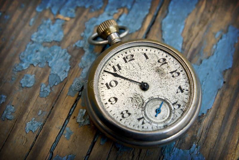 Antique pocket watch. Clock on a peeling blue wood floor royalty free stock image
