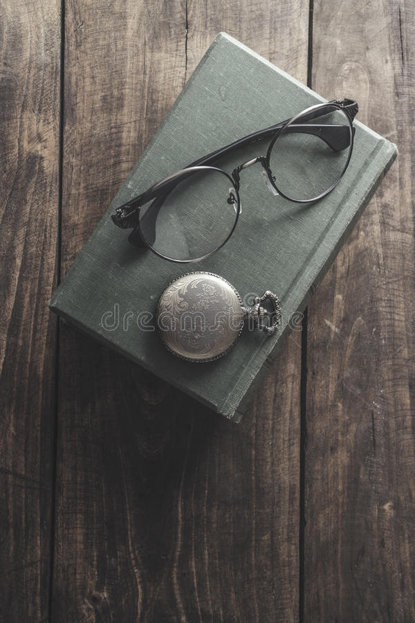 Antique pocket watch, glasses and book. Vintage still life stock photo
