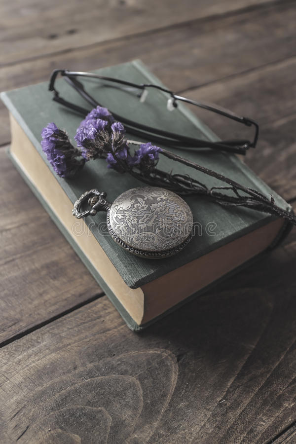 Antique pocket watch, glasses and book. Vintage still life royalty free stock photo