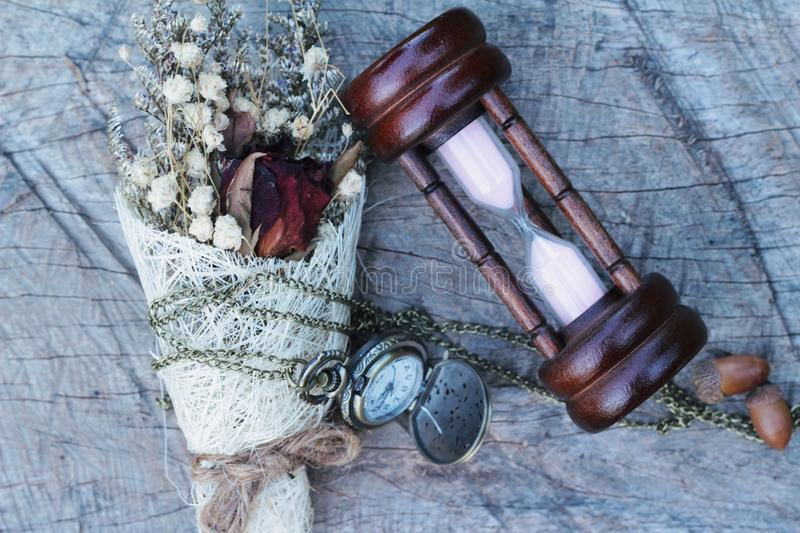 Antique pocket watch and hourglass with dried flowers. Antique pocket watch and hourglass with dried flowers royalty free stock photography