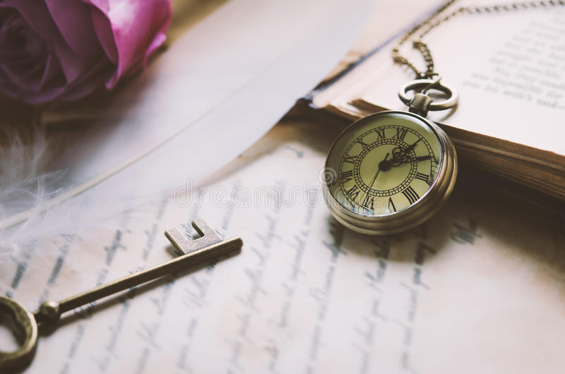 Antique pocket watch and old vintage key with vintage tone. Close up of antique pocket watch with old vintage bronze key and opened book on pile of letter stock photography