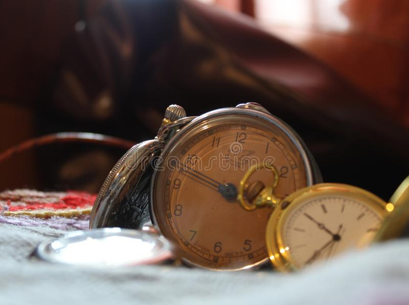 Antique pocket watch and vintage alarm clock lying on a colorful woolen blanket royalty free stock image