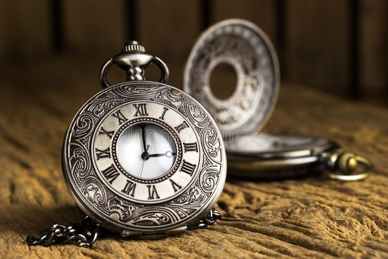 Antique pocket watch. Vintage Antique pocket watch on grunge wooden background stock image