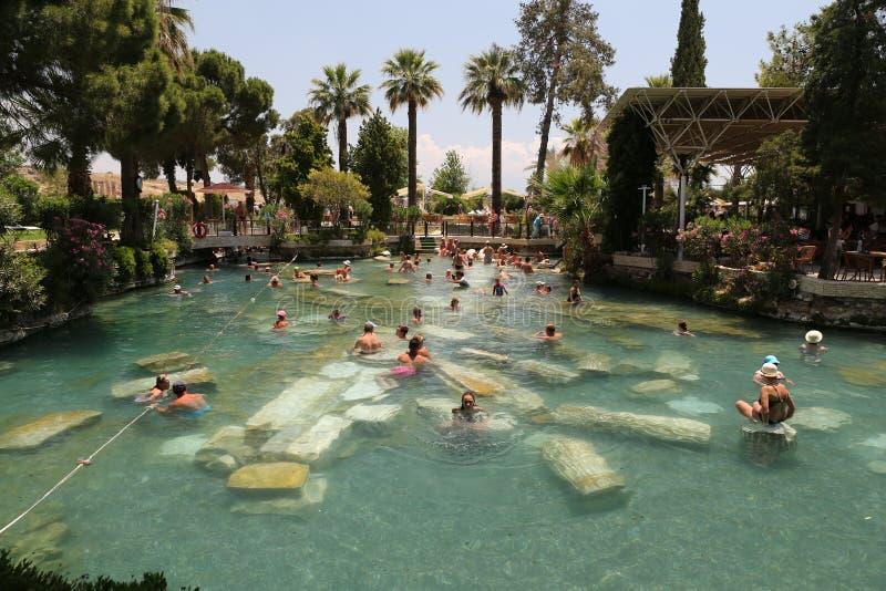 Antique Pool in Hierapolis Ancient City, Turkey. DENIZLI, TURKEY - JUNE 16, 2017: People in Antique Pool of Hierapolis Ancient City in Pamukkale. Pool was shaped royalty free stock photo