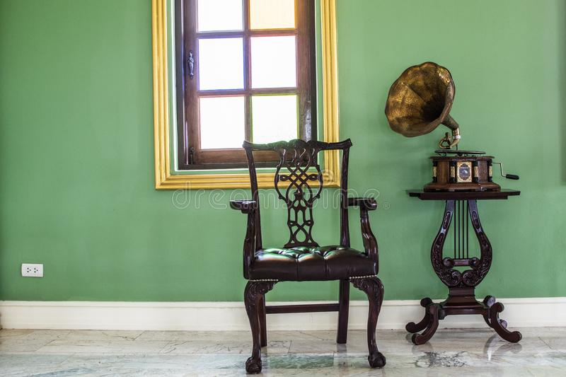 Antique record player and a chair in the corner. stock images