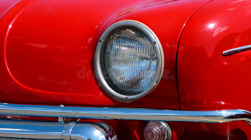Antique red car head light. Head-light and chromed bumper of a Renaud Dauphine's antique red car stock image